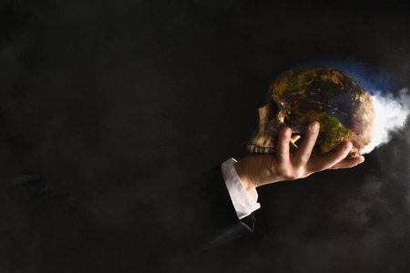 scruples: Businessman holding a burning globe While They changed into a skull