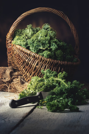 basket: fresh Kale in a Basket on a old wooden Table