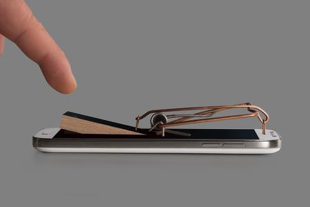 gatillo: Un smartphone simbólicamente como una trampa para ratones con un gatillo Foto de archivo