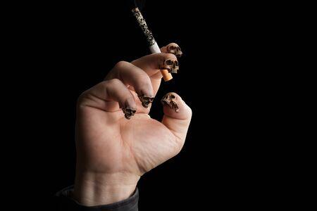 fingertips: Smoker hand with Skulls as Fingertips holding a cigarette