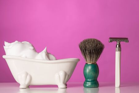 pink backdrop: Shaving Equipment on wooden Table and pink Backdrop