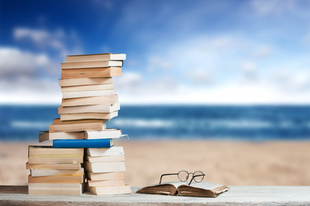 guides: Stack of Travel Guides before a Beach