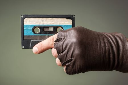 ddr: male hand with glove holding an old music tape Stock Photo