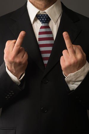 Politician with Tie in the Color of the USA shows the Finger
