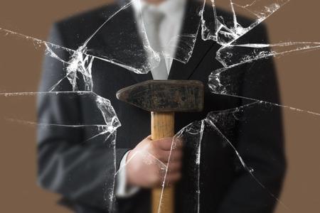 Business Man with Sledgehammer behind a broken Glass Pane Standard-Bild