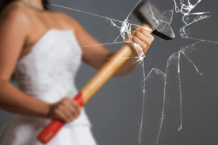 Bride with Sledgehammer behind a broken Glass Pane Standard-Bild
