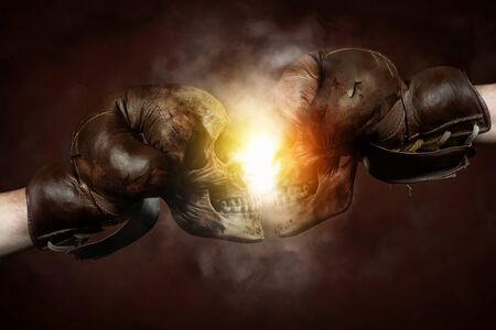 Two old brown boxing gloves with Skulls hit together