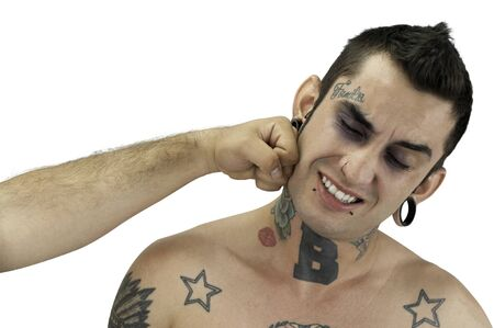 Young tattoo guy being kicked isolated on white background Stock Photo