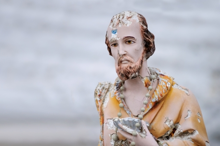 forgetfulness: Old statue of catholic saint abandoned and broken with copy space