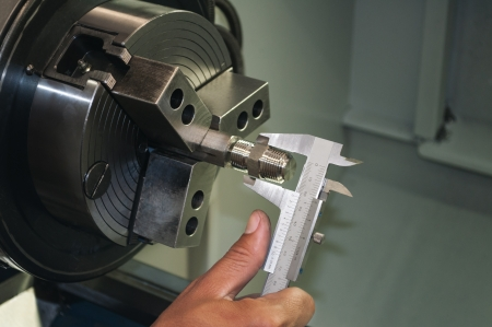 Worker measuring threaded part with caliper inside a CNC machine