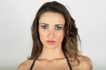 Pretty serious girl looking to camera on white background