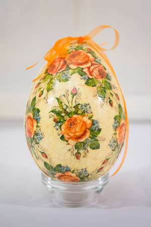 Easter egg decorated with flowers made by decoupage technique on light background photo