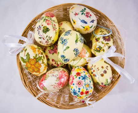 Group of colorful easter eggs decorated with flowers made by decoupage technique, in a basket on light background photo