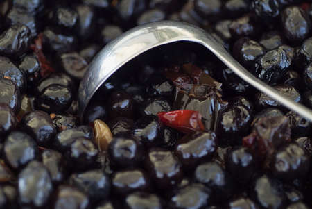 Black olives with red pepper and ladle photo