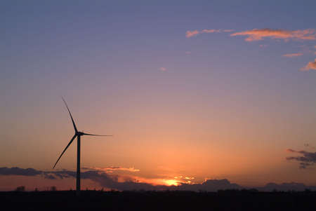 alternate: Single wind power generator against dramatic sunrise or sunset Stock Photo