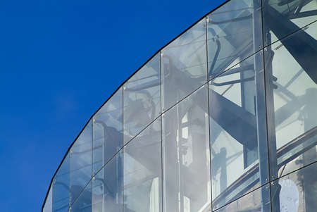 frontage: detail of glass clad curved building frontage against intense clear blue sky Stock Photo