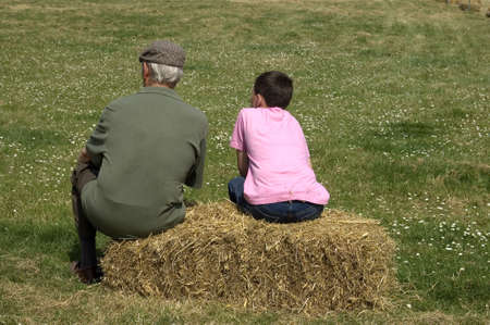 Man and boy sitting on straw bale in field. Space for text. photo