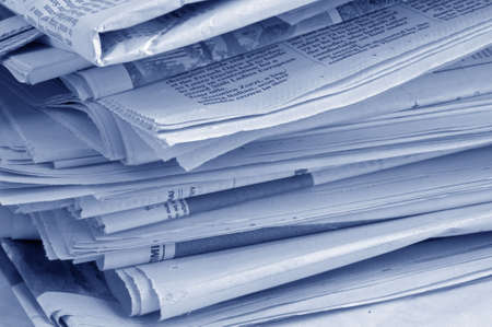 untruth: Close-up of jumbled pile of yesterdays newspapers, with blue tint.
