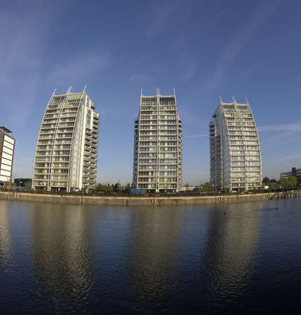 waterside: Three waterside luxury apartment blocks against clear blue sky