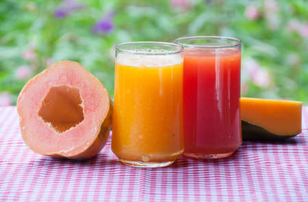 papaya flower: Smoothie papaya juice on table with garden flower background