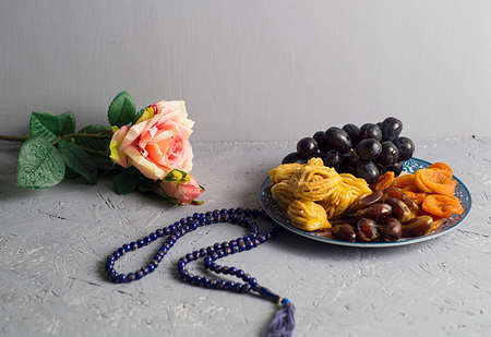 Sweets, dates, dried apricots on a plate. Flower. The concept of Ramadan, iftar.