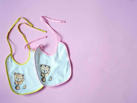 White baby bibs with pink and yellow border, on pink background Foto de archivo - 123651318