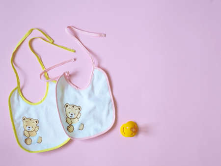 White baby bibs with pink and yellow border, on pink background Foto de archivo - 123651320