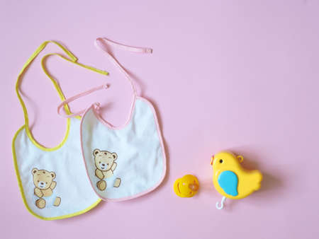 White baby bibs with pink and yellow border, on pink background Foto de archivo - 123651321