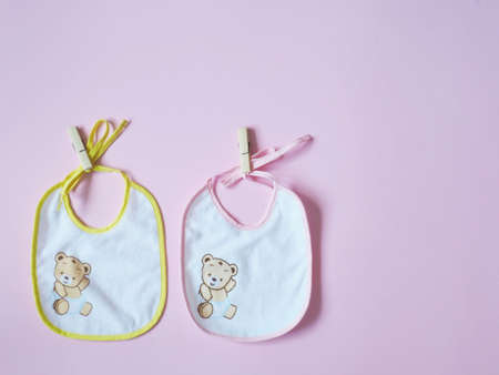White baby bibs with pink and yellow border, on pink background Foto de archivo - 123651323