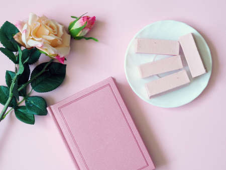 Book, tea, rosary, sweets on a plate on a pink background. Flower. The concept of Ramadan, iftar.