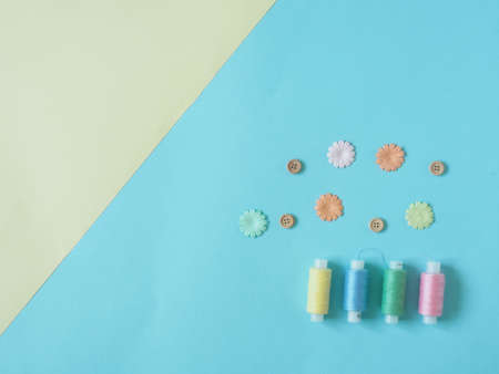 Spools of thread, buttons. Accessories for sewing on blue and yellow background. The Duo's backgrounds. Set for needlework in the top view. 写真素材