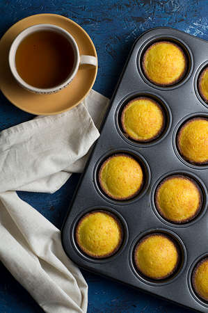 Muffins with tea on a blue background