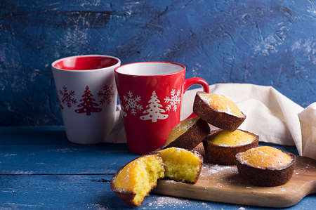 Cupcakes and mug with winter ornament on blue background