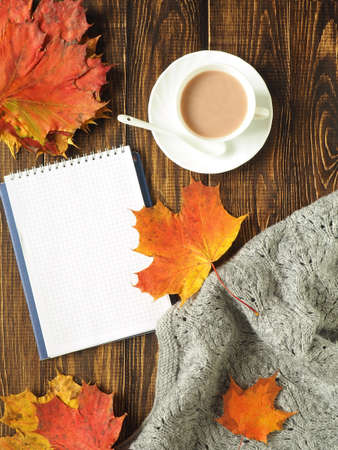 Autumn. flat lay. Sheets, a warm scarf, a Cup of tea and notebook with pen on wooden rustic background, overhead view with copy space Stock Photo