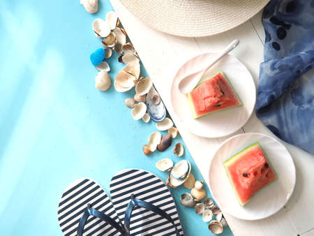 Concept of summer holidays with beach items on a blue background. The view from the top.