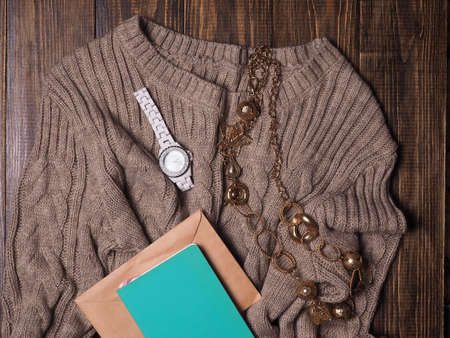 Brown knitted sweater, notebook, clock on a dark wooden background, top view. Womens clothing. Flat lay, a cozy concept Stok Fotoğraf