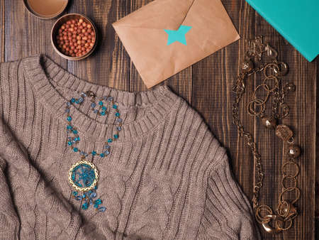 Female outfit on a wooden background. Cosmetics, jewelry.Flat lay.