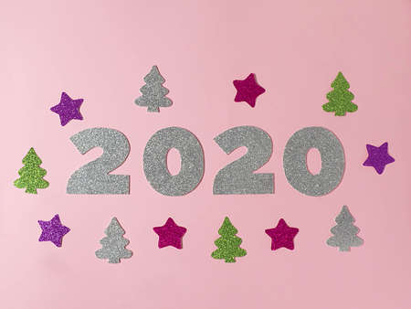 Celebrating the new year 2020. Silver mother-of-pearl paper, number 2020, pink and lilac stars, green and silver Christmas trees and confetti on a pink background. Flat lay. Stock Photo