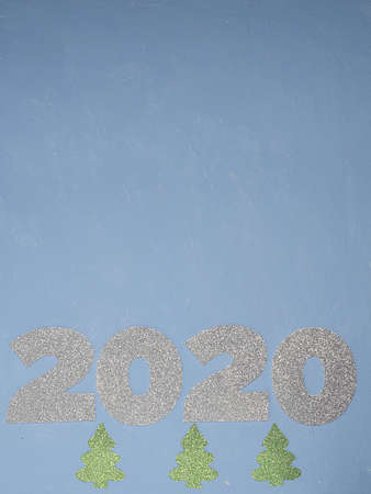 Celebrating the new year 2020. Silver mother-of-pearl paper, number 2020 on a blue background. Flat lay.