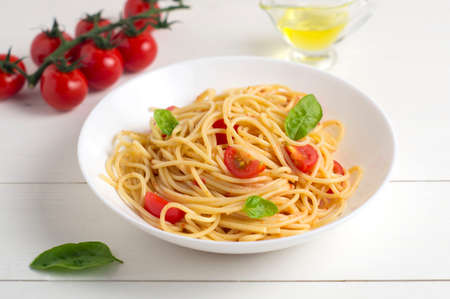 Spaghetti with tomatoes and Basil on a white wooden background. Healthy diet.