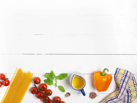 Spaghetti with tomatoes and Basil on a white wooden background. Ingredients. Healthy diet.