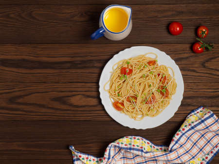 Spaghetti with tomatoes and micro-greens on a dark wooden background. Healthy diet. Flat lay. Zdjęcie Seryjne