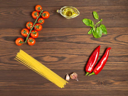 Spaghetti with tomatoes and Basil on a dark wooden background. Ingredients. Healthy diet. Flat lay. Zdjęcie Seryjne