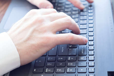 Close-up of a businessman typing on a laptop. Business concept, business at home.