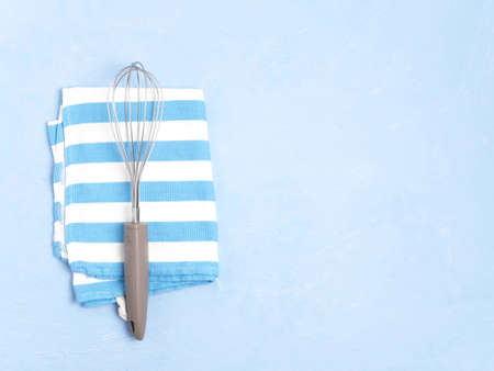 Whisk and towel on a blue concrete background. Copy space.
