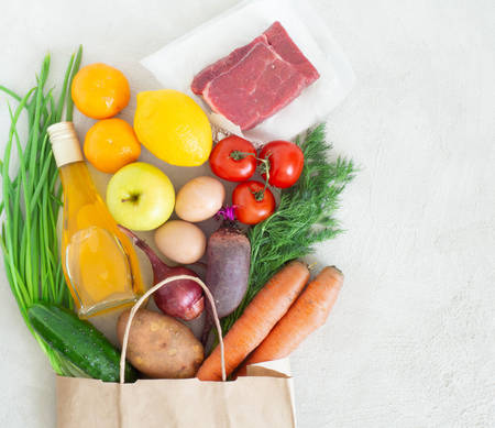 Paper bag with various healthy food on a gray concrete background, flatley