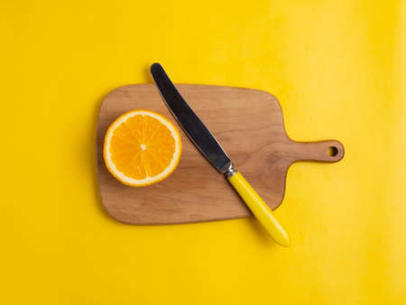 The orange is sliced and cut with a yellow knife on a Board on a yellow background.