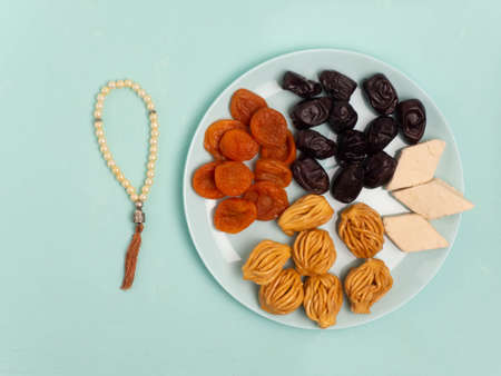 Flatley with rosaries, sweets, dates. The Concept Of Ramadan.