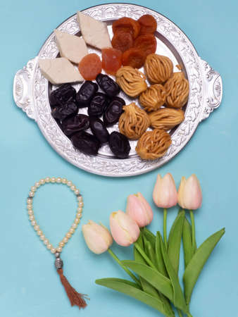 Flatley with rosaries, sweets, dates and tulips. The Concept Of Ramadan. Banque d'images