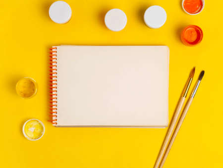 Items for drawing on a yellow background: paints, brushes, Notepad. School supplies. A copy of the space.Copy space. Flat lay.